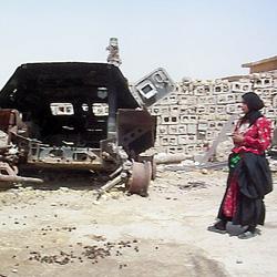 Frau im Irak vor einem Schrottpanzer